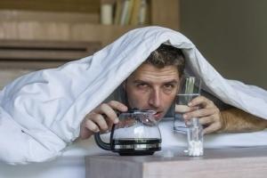 Giovane uomo sotto le coperta con aria di malessere a causa dei postumi della sbronza.