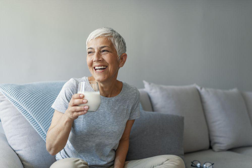 Donna anziana beve un bicchiere di latte