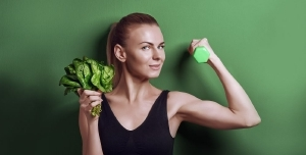 Giovane donna con in mano un mazzo di spinaci e un peso