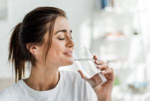 Donna che beve un bicchiere d'acqua a occhi chiusi