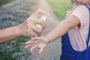 Spray contro le zanzare spruzzato su braccio di un bambino