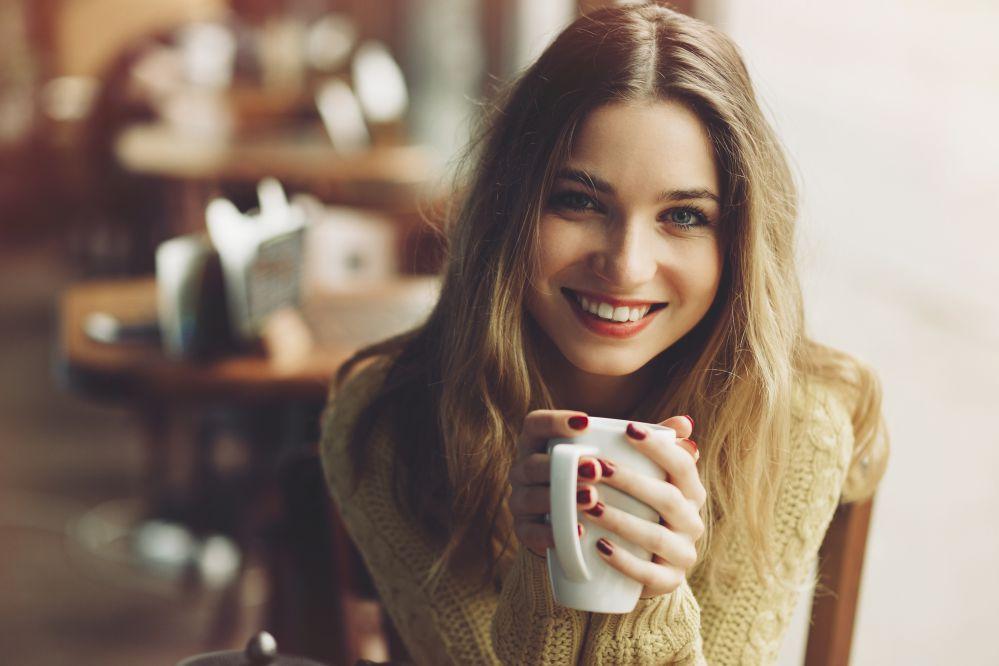 Ragazza con un maglione e una tazza di latte caldo in mano - Il latte produce muco?