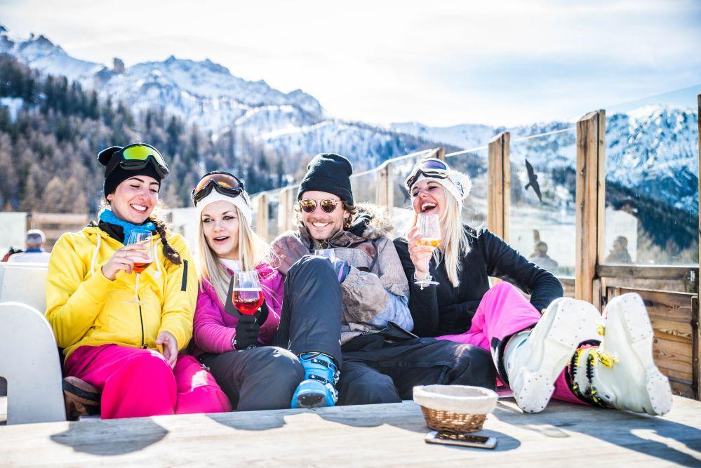 Gruppo di persone in abito da sci bevono alcol sulla neve
