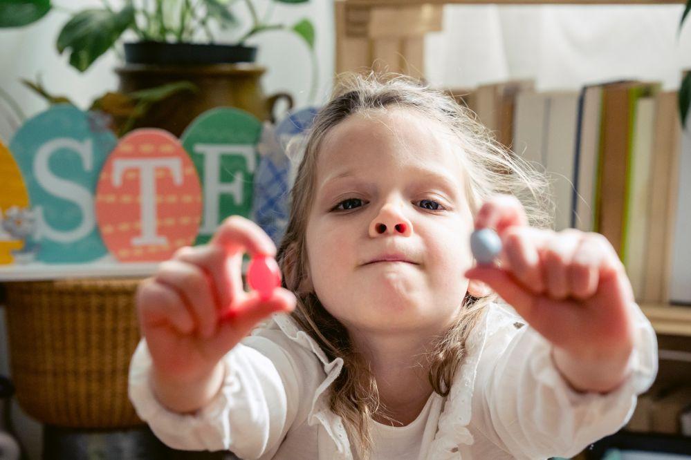 Bambina di 3 anni con una caramella in ciascuna mano
